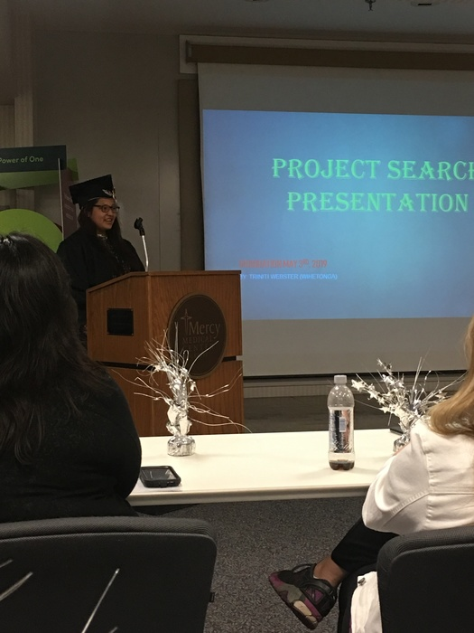 Triniti giving a presentation for graduation.